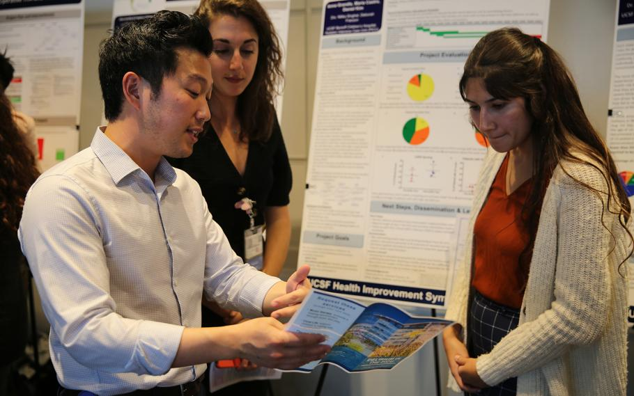 Medical students (from left) Daniel Kim, Anna Grandis and Maria Castro display their clinical microsystem clerkship project at a symposium on Nov. 18, 2019.